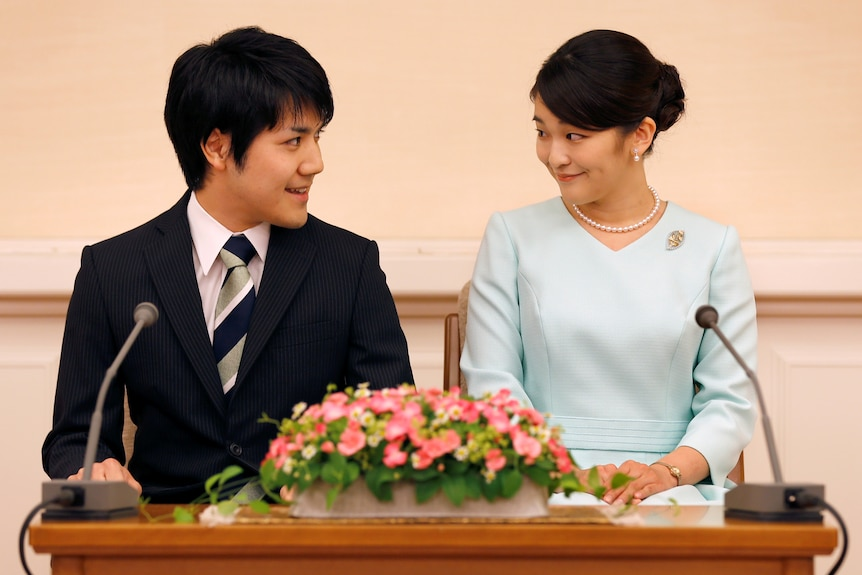 Princess Mako and Kei Komoru sit at a table and look lovingly into each other's eyes.