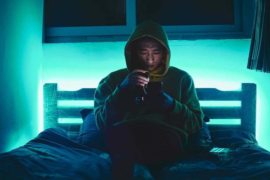 Man in hoodie looking at phone while sitting on bed for a story about what to do when you're being stalked.
