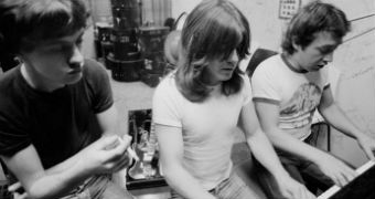 AC/DC producer George Young sitting at a piano with brothers Malcolm and Angus Young.