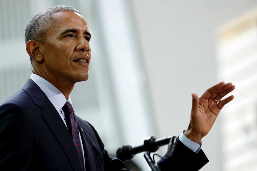 Barack Obama raises his hand as he speaks.