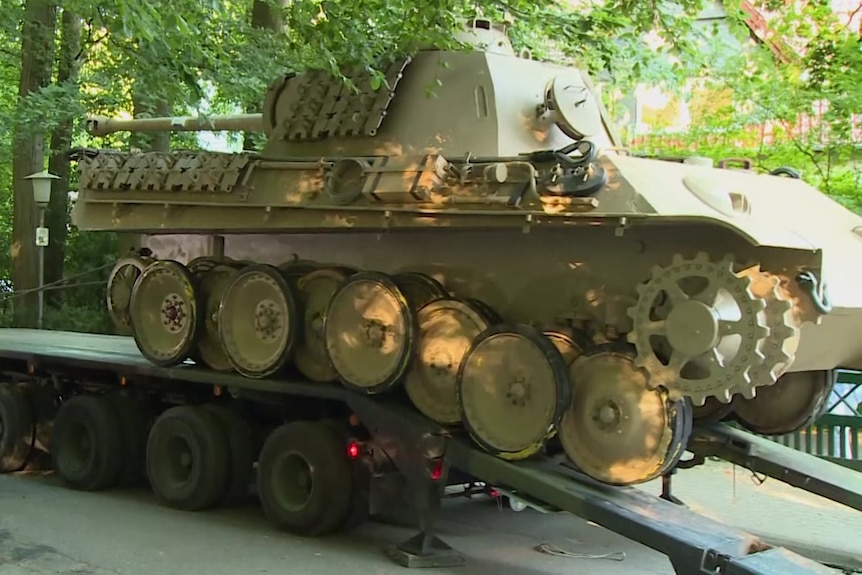 A brown tank is loaded onto a trailer.