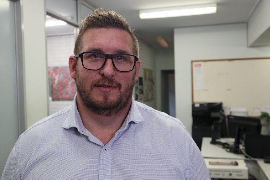 A man with a beard and moustache wearing glasses looks at camera