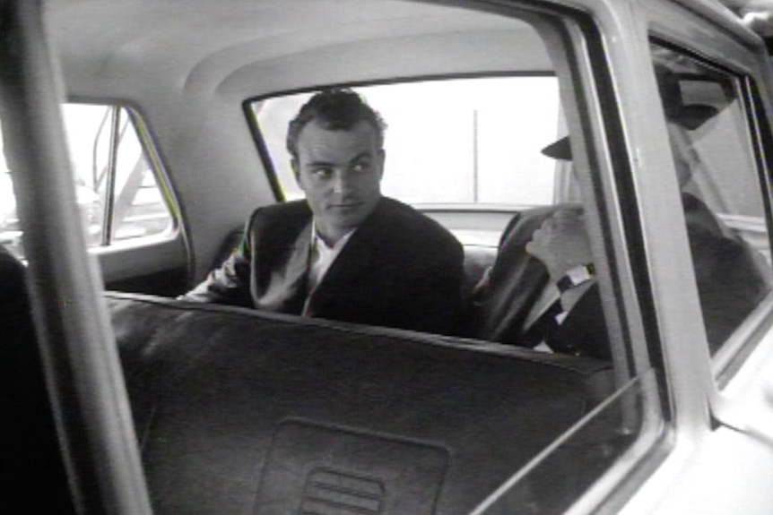 A historical black-and-white image of a criminal dressed in a suit in the back of an unmarked police vehicle