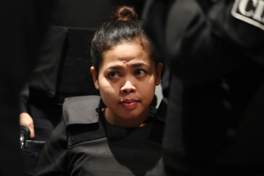 A woman looks off camera as she is surrounded by authorities.