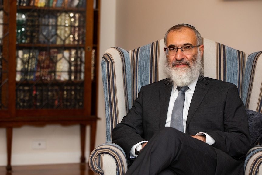 Rabbi Marcus Solomon sitting down in an armchair indoors posing for a photo and smiling.