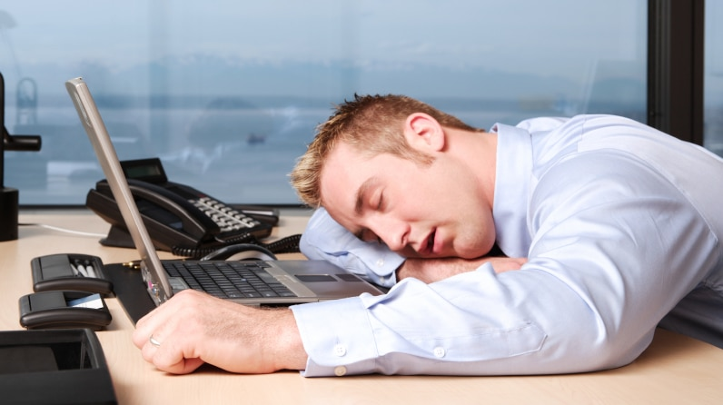 A man lying over his desk at work.