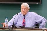 Ken Fleming sitting at a desk during NT Parliament estimates.