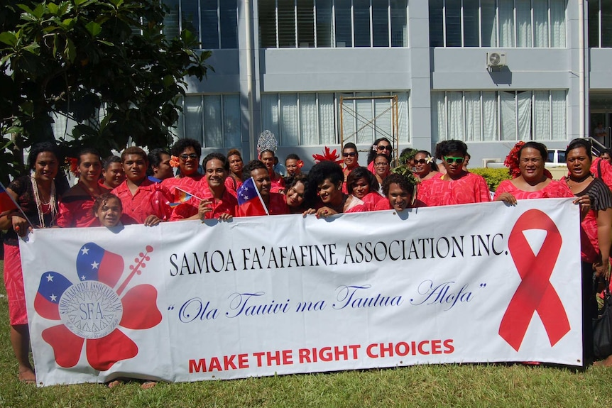 A group of people from the Samoa Fa'afafine Association wearing red with a banner against AIDS.
