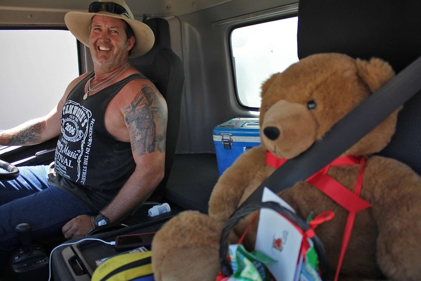 Truck driver Allan Hughes sits next to a stuffed teddy bear in the cabin of a truck.
