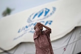 A girl standing in front of a UN shelter for the internally displaced Rohingya in Myanmar.