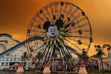 An orange sky with dark smoke is seen over the rollercoasters and Mickey Mouse ferris wheel at Disneyland.
