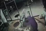 A burglar attempts to break open a cash register.