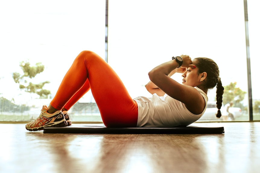 Woman with a plaited ponytail wearing red tights and white single in the process of doing a sit up.