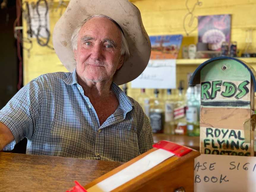 An elderly man with a big white white sits behind a bar, with a sign in book and RFDS fundraiser in the foreground.