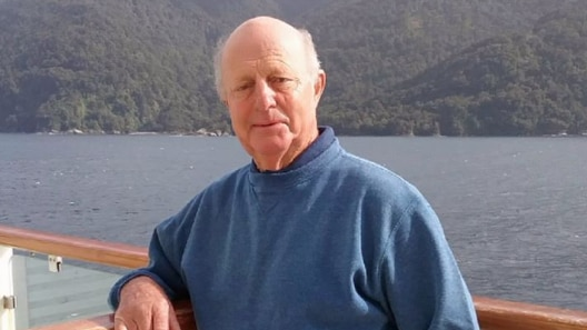 An old man leans over the railing of a boat, with a lake and hills in the background.