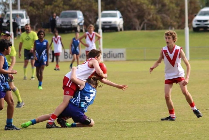 Action shot of Tayah Palmer in the number 3 blue jersey, tackles a boy in a red jersey on a football pitch.