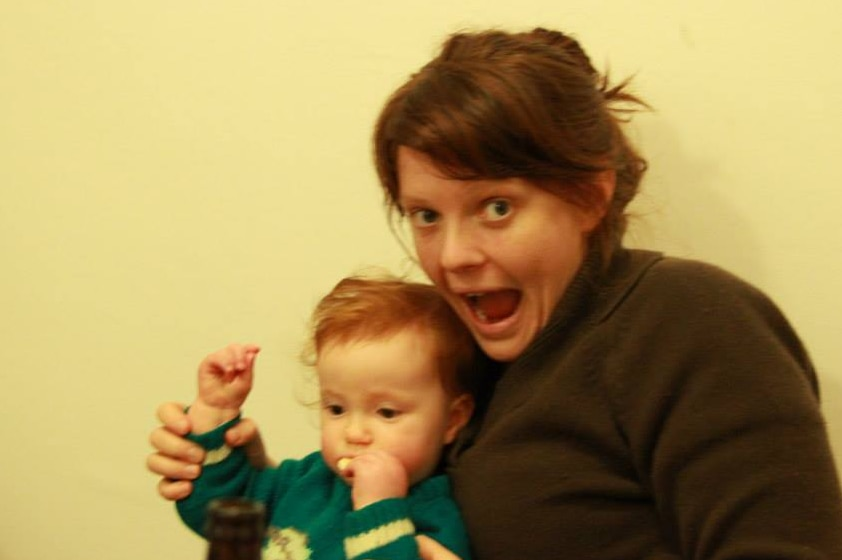 Slightly blurred photo of woman with open-mouthed happy gape, holding a small child on her lap.
