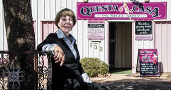 Older woman wearing a suit and with a slight smile sitting in front of a pink 'Questa Casa' sign.