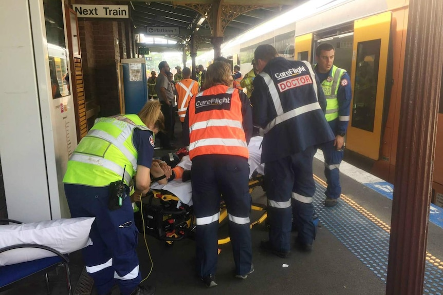 People being taken off a train and put on stretchers.