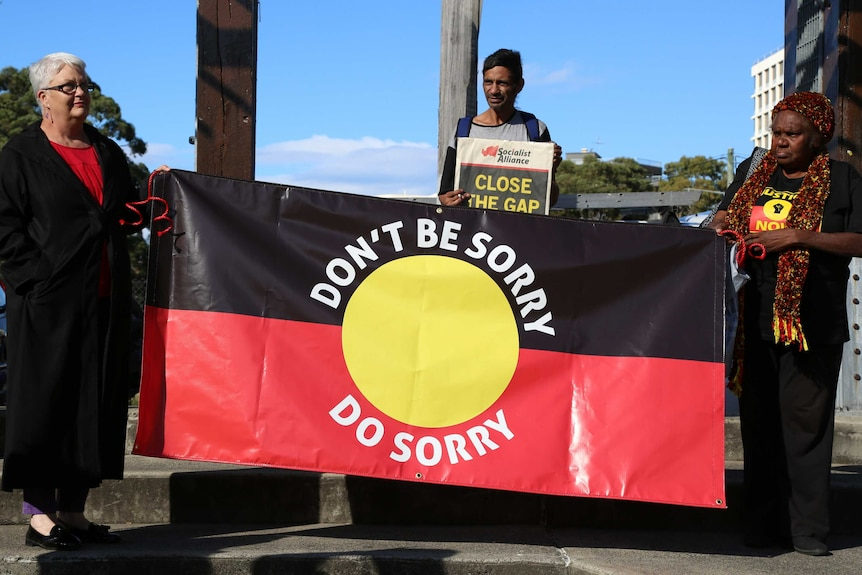 Two women hold an Australian Indigenous flag emblazoned with the words 'don't say sorry, do sorry'.