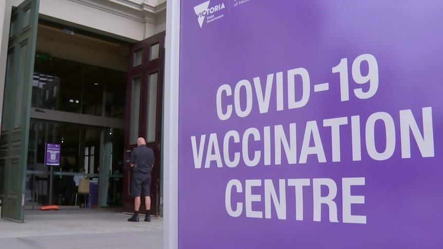 A purple sign outside a building which says COVID-19 vaccination centre.