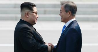 Kim Jong-un and Moon Jae-in shake hands.