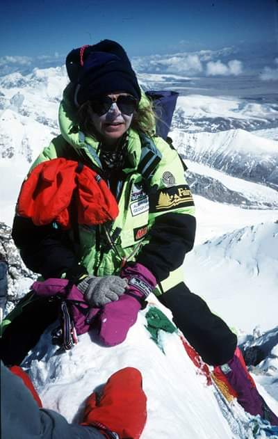 Brigitte Muir with white zinc or her face, sunglasses, beanie and snow clothing, on a snow-capped peak with mountain surrounds.
