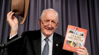 Tim Fischer smiles as he holds up his Akubra hat and a copy of his book, Trains Unlimited.