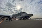 A cruise ship against a cloudy sky.