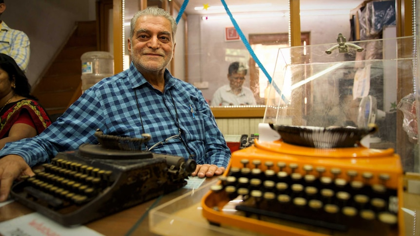 An older man in a buttoned shirt sits, relaxed, with his arm stretched next to one of two old typewriters on a table.
