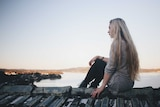 Young woman with long blonde hair sitting looking out to sea.
