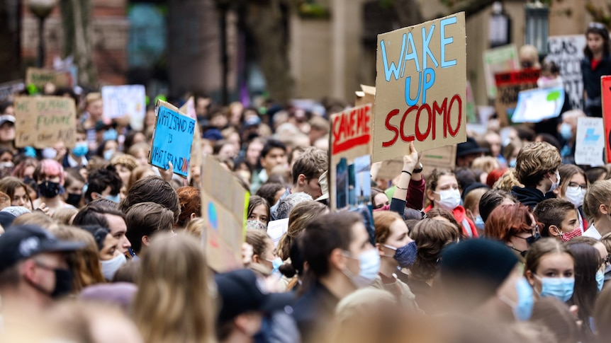 """A large crowd of young people hold up signs in protest. One reads """"WAKE UP SCOMO""""."""