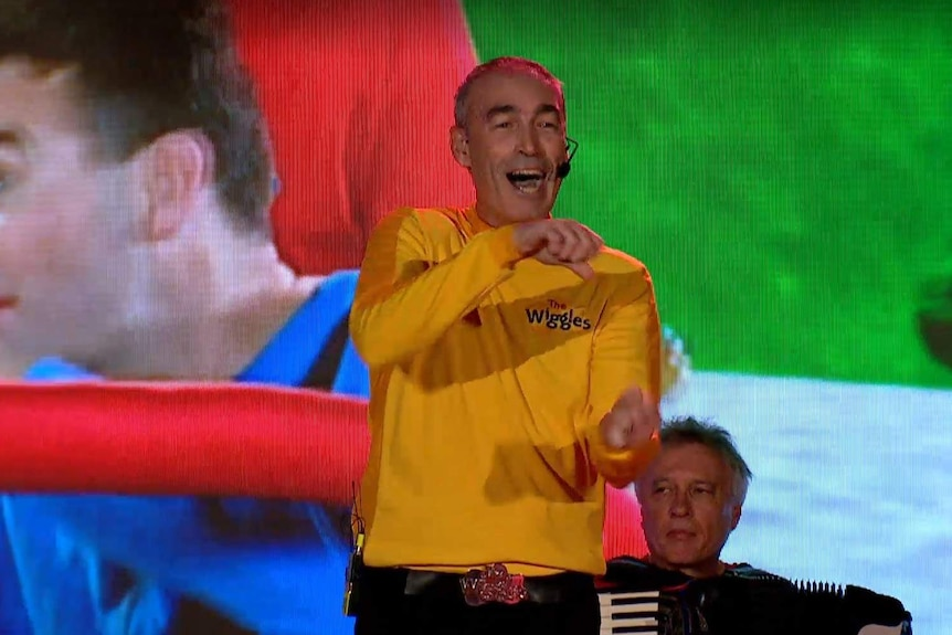 Greg Page wearing a yellow Wiggles costume performing on stage