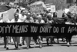A group of older women walk the streets with a large banner that says 'Sorry means you don't do it again'