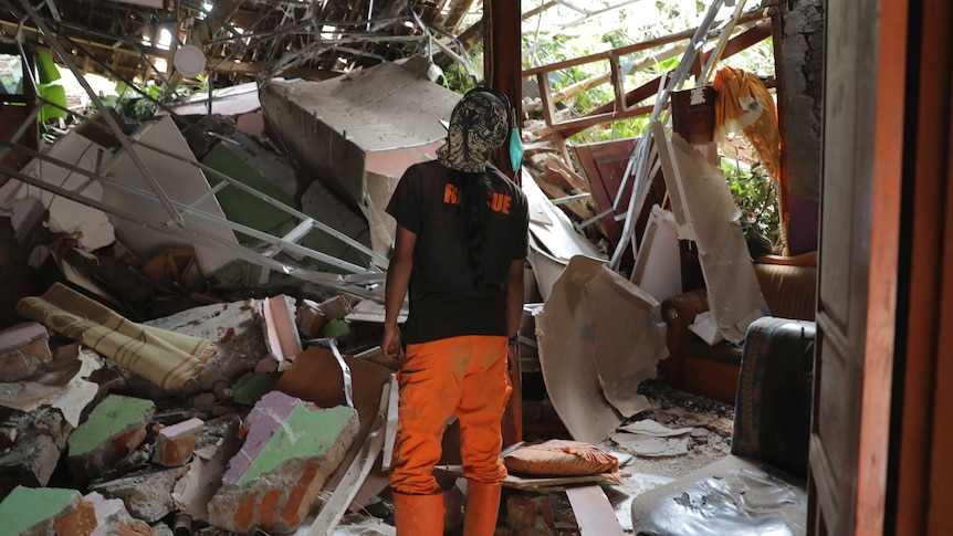 A person with their back to the camera stands amid the rubble of a house.