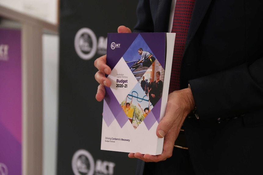 A man's hands holding the ACT Budget for 2020-21.