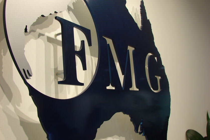 Photo of the black and white FMG logo rendered large on an office wall