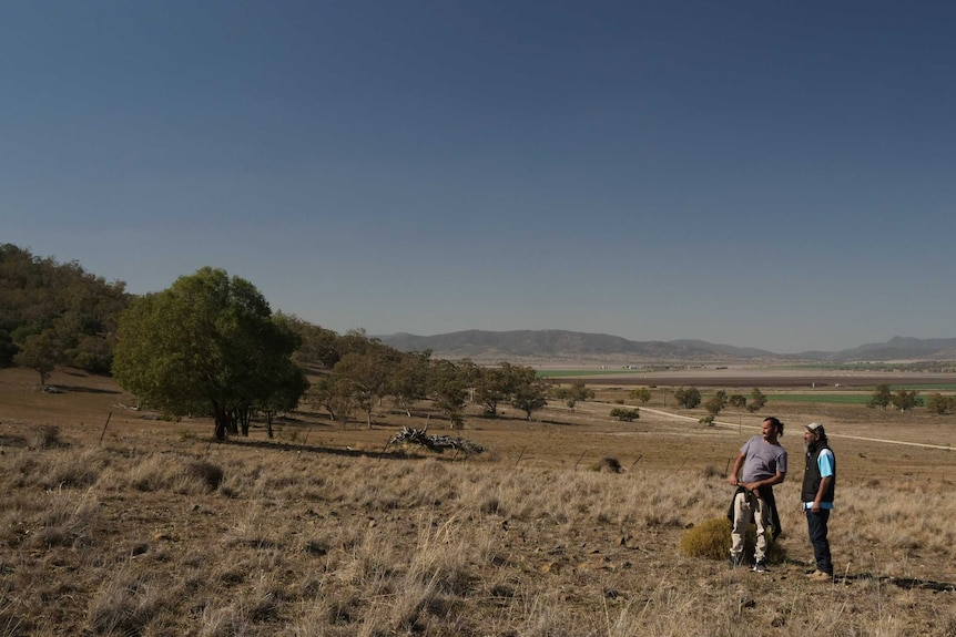 Steve Talbott (r) pictured on the Shenhua mining lease, looking up a hill.