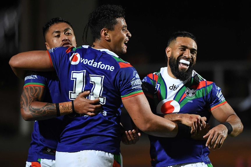 Three Warriors NRL players celebrate a try scored against the Manly Sea Eagles in Sydney.