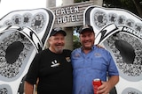 Two men, Lionel Knott and Gavin Butlin, stand in front of a large pair of black and white thongs.