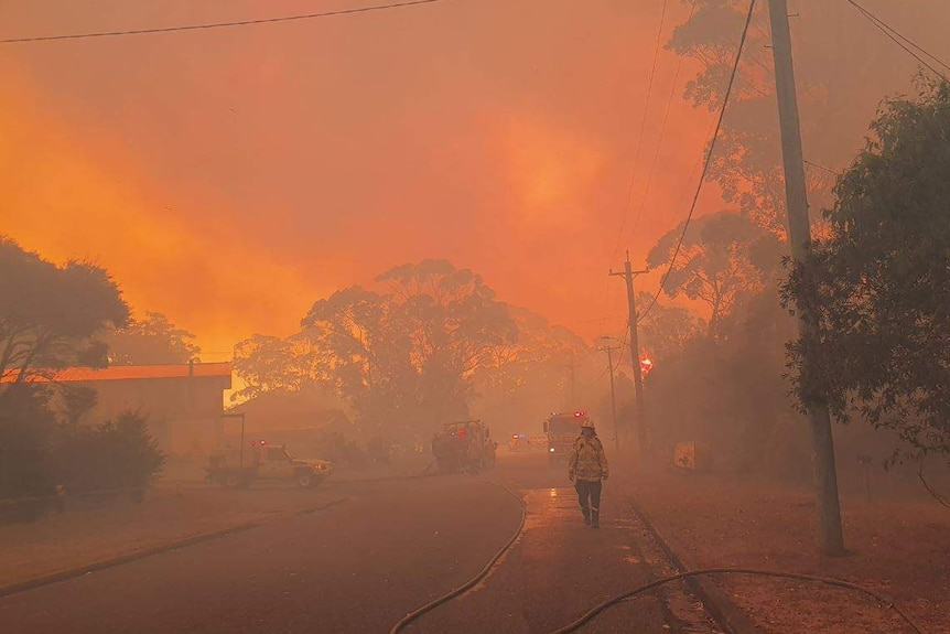 A firefighter walks along a street with a blood red sky and smoke behind him.
