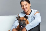 Sam Kerr sits on a white sofa, bare foot wearing a tracksuit, with a boxer dog on her lap.