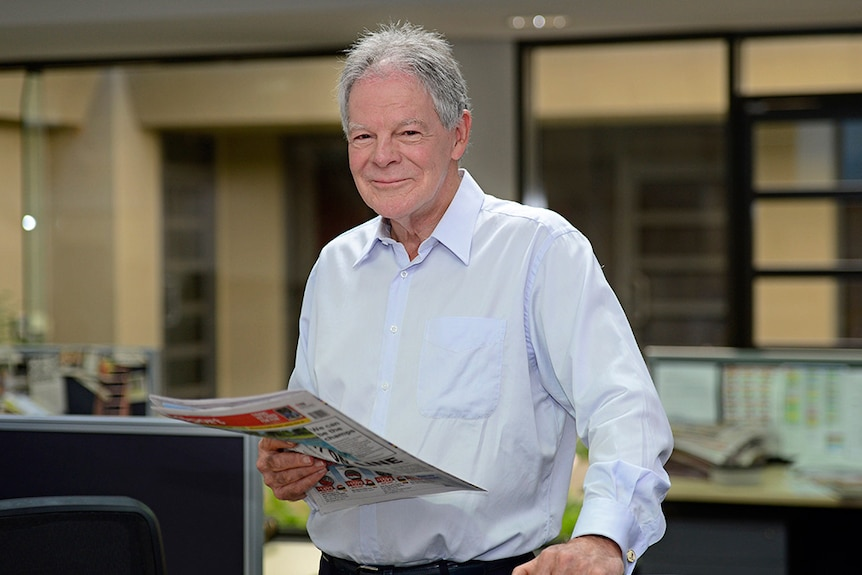 A man smiles while holding a newspaper.