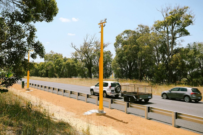 Two cars on a highway, one towing a trailer, pass by a pole mounted speed camera.