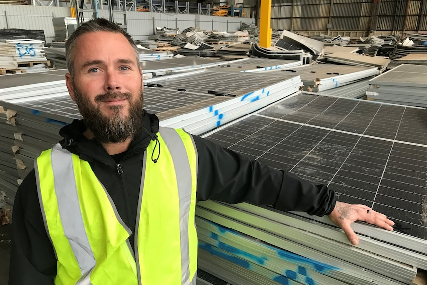 A man in a high-viz vest rests his arm on a stack of old solar panels inside a warehouse.