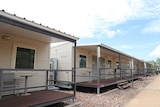 A photo of the Howard Springs quarantine facility, showing a row of dongas each with a small verandah out the front.