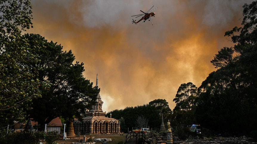 A waterbombing helicopter flies over a monastery.