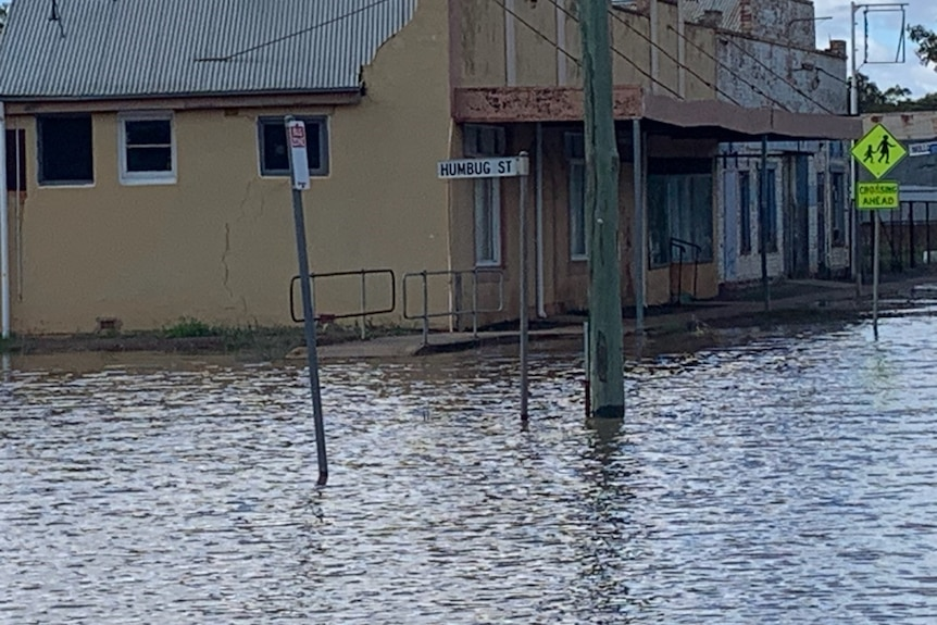"Floodwater covers streets in front of buildings and a streetsign reading ""Humbug st""."