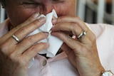 A woman blows her nose.
