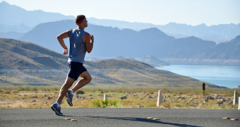 Man running on road with lake and mountains behind